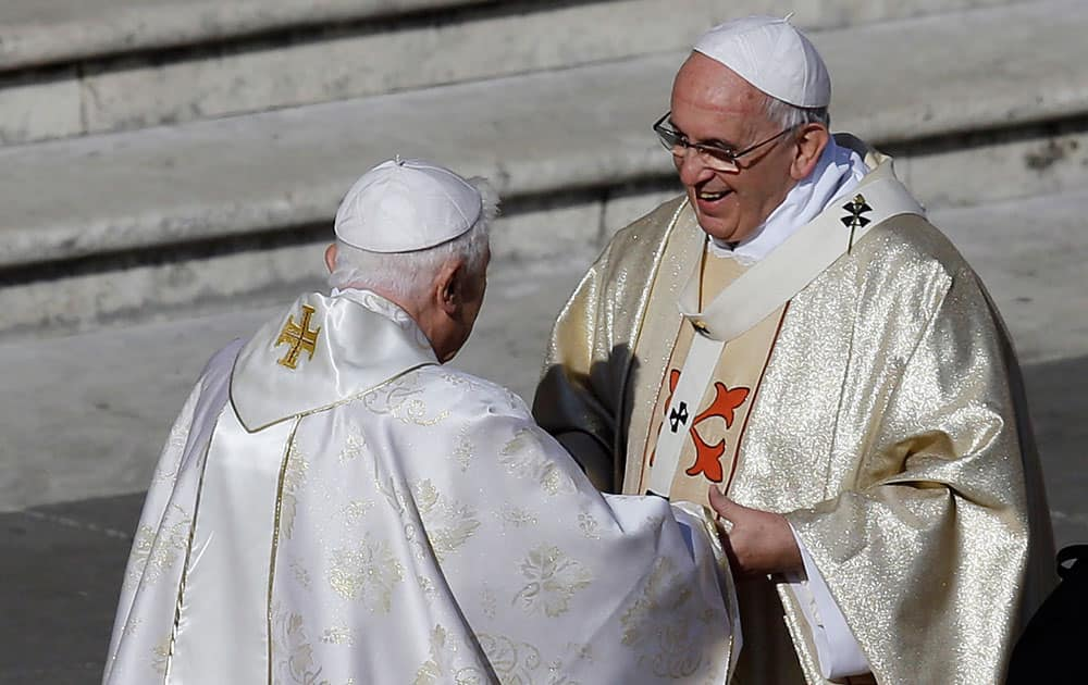 Pope Emeritus Benedict XVI, left, greets Pope Francis prior to the start of the beatification ceremony of Pope Paul VI and a mass for the closing of a two-week synod on family issues, in Saint Peter's Square at the Vatican.