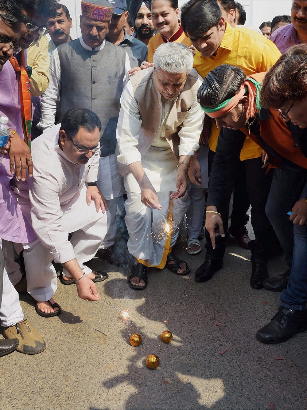 BJP general secretaries J P Nadda and Ram Lalji with party supporters burst crackers while celebrating the partys victory in Haryana and Maharashtra Assembly elections, in New Delhi.