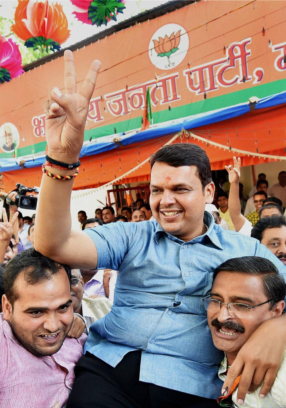 BJP leader Devendra Fadnavis gestures victory sign, along with party workers while celebrating win in the Assembly elections in Mumbai.