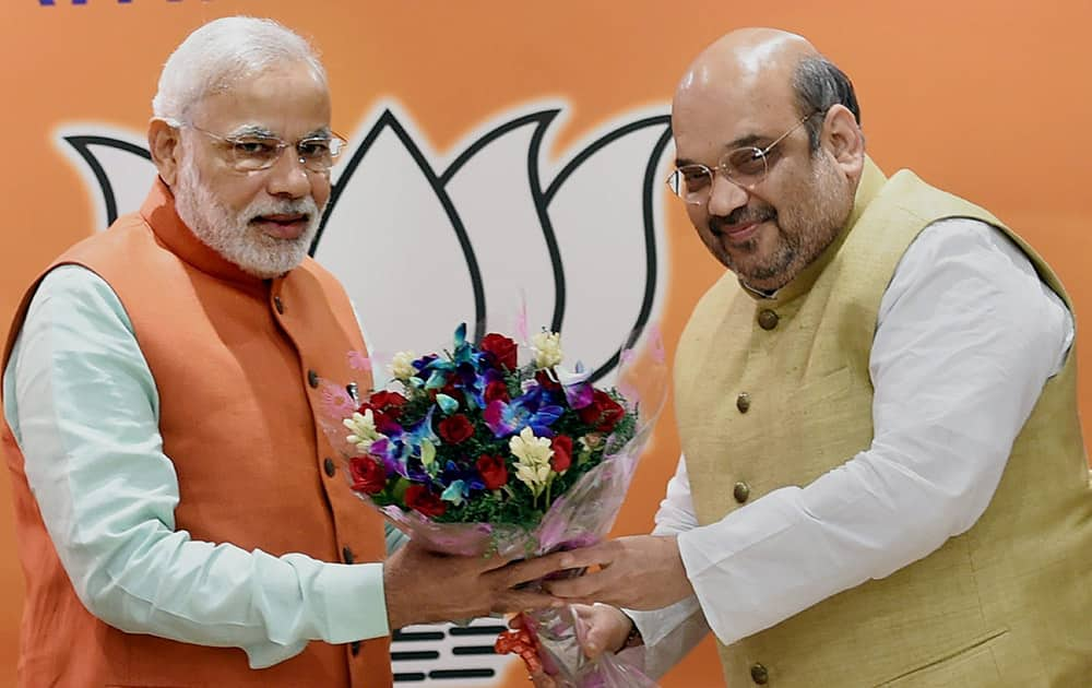 PM Narendra Modi being welcomed by BJP President Amit Shah during the partys parliamentary board meeting to assess the assembly poll results.