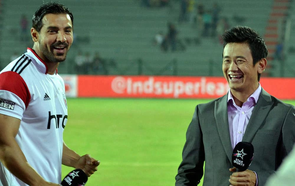 John Abraham, co-owner of North East United Football Club with former Indian Football player Bhaichung Bhutia shares a light moment during the ISL match against Goa FC, at Indira Gandhi Athletic Stadium in Guwahati.