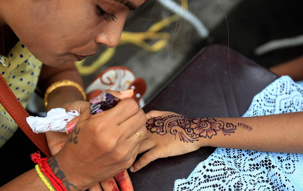 An artist applies henna on the hand of a Malaysian ethnic Indian girl for the upcoming Diwali, or the Hindu festival of lights in Klang, outside Kuala Lumpur, Malaysia.