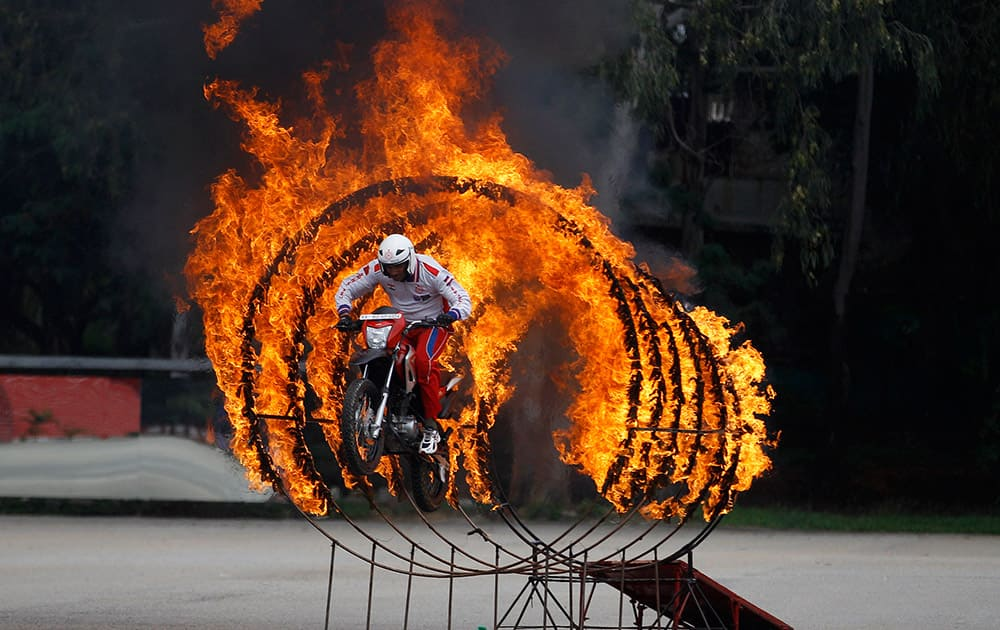 A member of Shwet Ashw, the motorcycle display team of the Indian army, jumps through a fire ring as he performs a daredevil stunt during the platinum jubilee celebrations of Corps of Military Police in Bangalore.