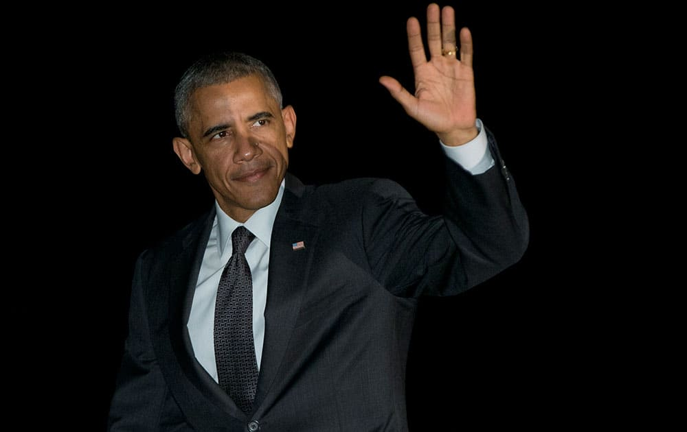 President Barack Obama waves as he walks from Marine One, across the South Lawn to the White House in Washington, as he arrives from Chicago.