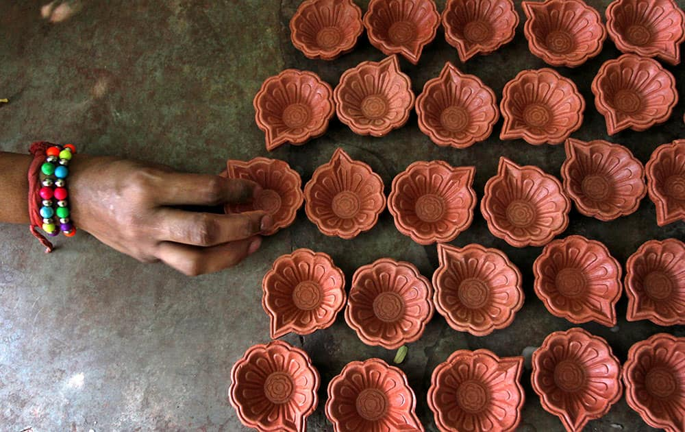 An Indian blind girl arranges earthen lamp casings ahead of Diwali festival in Ahmadabad.