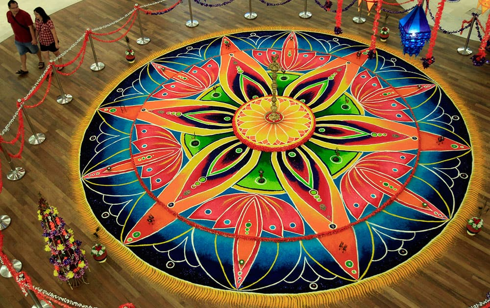 Shoppers walk past an Indian traditional creative artwork `Kolam,` a form of sandpainting, for the upcoming Diwali, or the Hindu festival of lights.