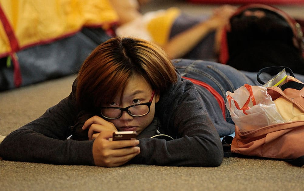 A pro-democracy student protester looks up from her smart phone at the protest site in the Mong Kok district of Hong Kong.