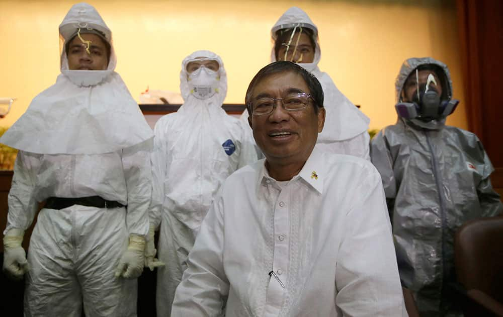 Philippine Health Secretary Enrique Ona sits in front of medical health workers wearing different types of `Ebola suit` during a media tour of the Research Institute for Tropical Medicine facility to show the Government's readiness in the still Ebola-free country at Alabang, Muntinlupa city, south of Manila, Philippines.
