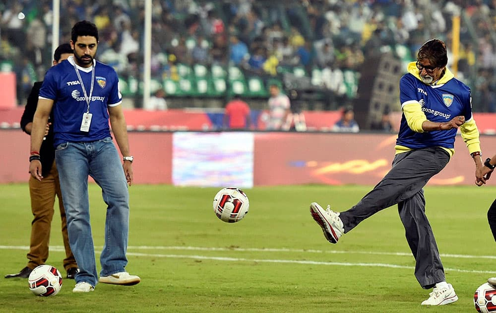 Bollywood Actor Amitabh Bachchan kicks a football as Chennaiyin FC co owner Abhishek Bachchan looks on during the Indian Super League match between Chennaiyin FC and Kerala Blasters FC in Chennai.