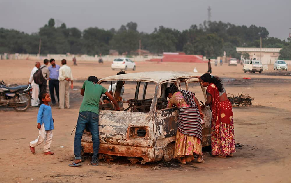 Waste pickers look for reusables from the debris of a damaged vehicle at a fair ground where a massive fire Tuesday evening gutted down a temporary fire crackers market set up for the Diwali festival in Faridabad.