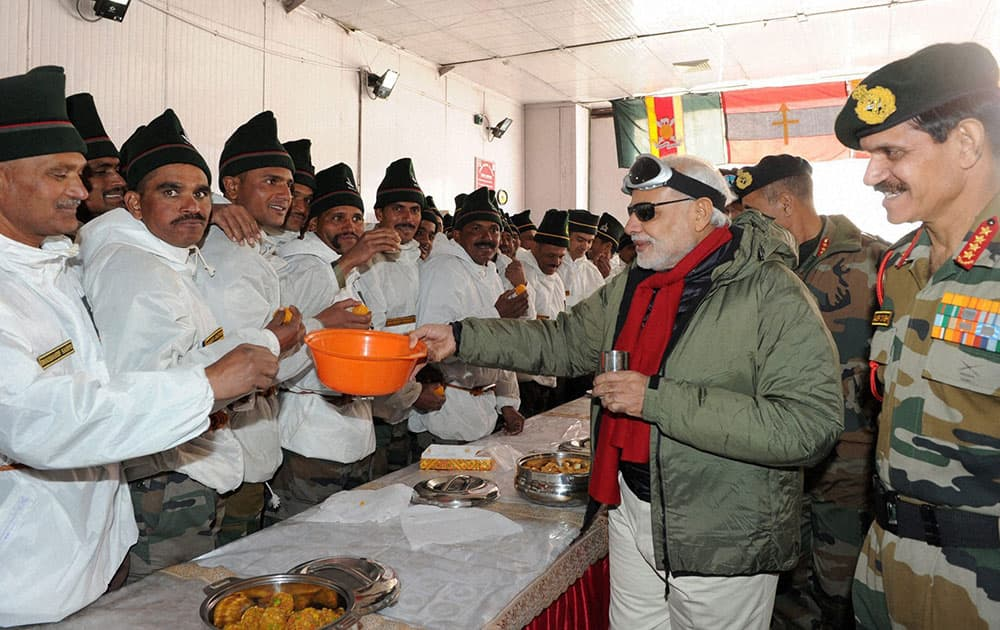 Prime Minister Narendra Modi sharing sweets with the Officers and Jawans of Indian Armed Forces during his visit to Siachen on the occasion of Diwali on Thursday.The Chief of Army Staff, General Dalbir Singh is also seen.