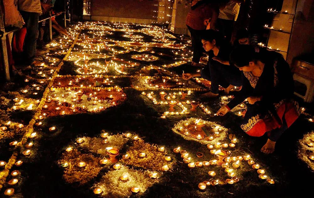 Devotees light lamps in Keshev Dev Temple premises during Diwali Festival celebration in Mathura.