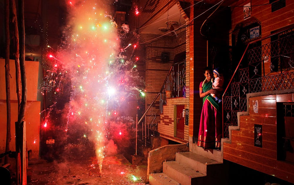 An Indian woman holds her child and watches a firecracker light up during Diwali, the festival of lights, in New Delhi.