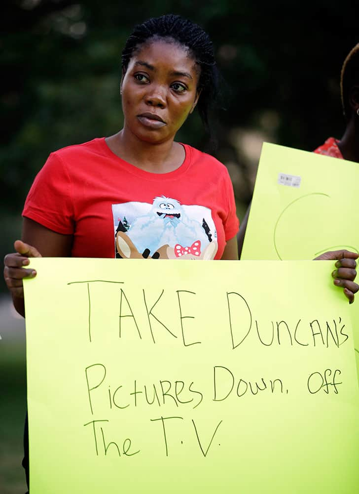 Youngor Jallah, daughter of Louise Troh, who was the fiance of Thomas Eric Duncan stands outside of Texas Health Presbyterian Hospital Dallas holding a sign during a protest, in Dallas.