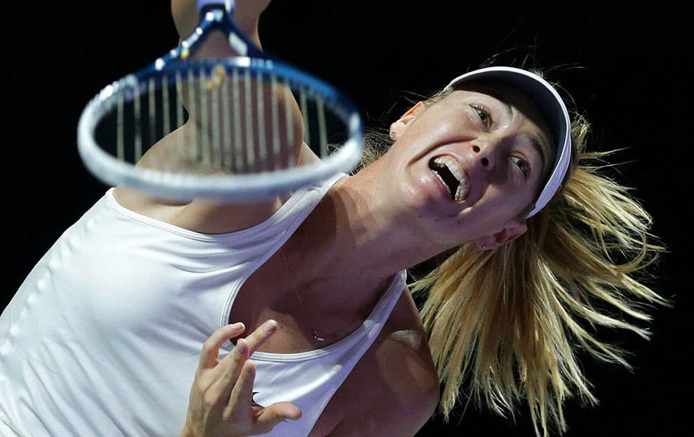 Russias Maria Sharapova serves to Polands Agnieszka Radwanska during their singles match at the WTA tennis finals in Singapore.
