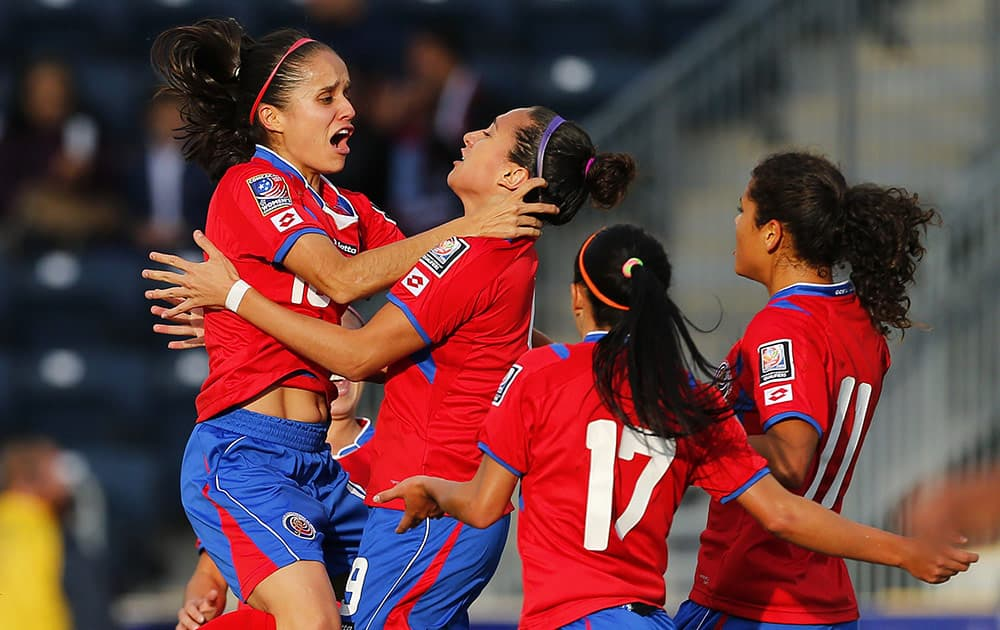 Costa Rica midfielder Katherine Alvarado (16) jumps into the arms of forward Carolina Venegas (9) after Venegas' goal in the first half against Trinidad and Tobago during a CONCACAF semifinal soccer match in Philadelphia, Pa