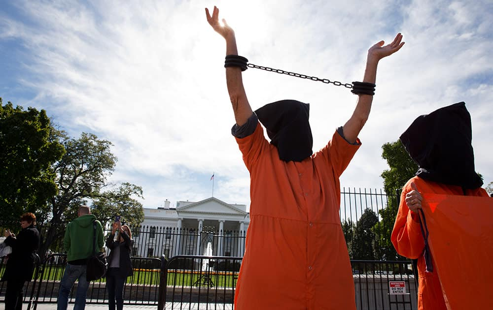 People protest against 'indefinite detentions' at Guantanamo Bay detention center and Bagram prison, while in front of the White House in Washington.