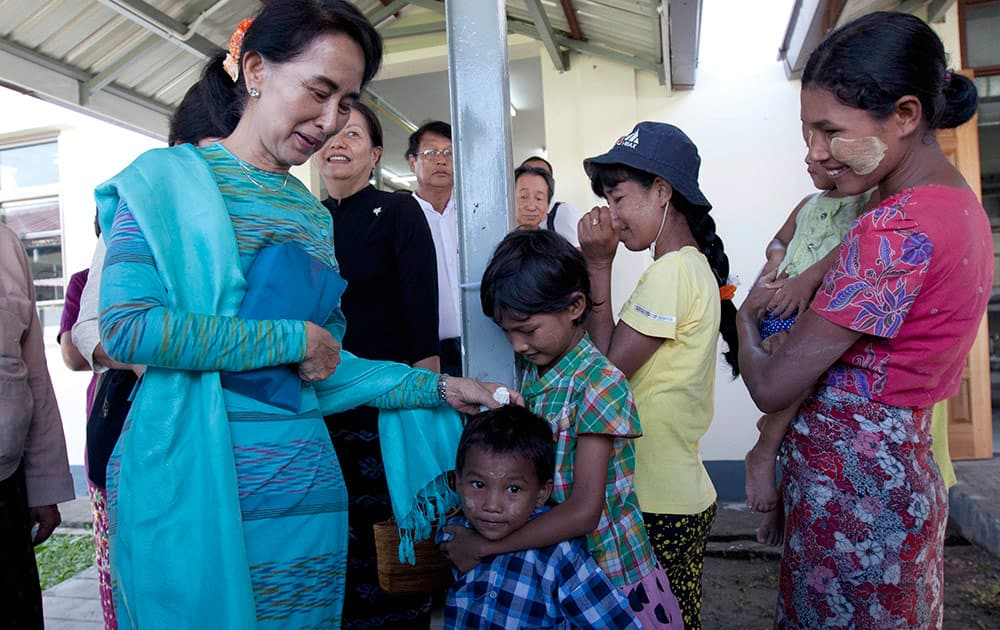 Myanmar opposition leader Aung San Suu Kyi, greets her supporters during the opening ceremony of Hospitality and Catering Training Academy of Daw Khin Kyi Foundation, late mother of Suu Kyi, in Kaw-Hmu, her constituency for a parliament seat, in Yangon, Myanmar.