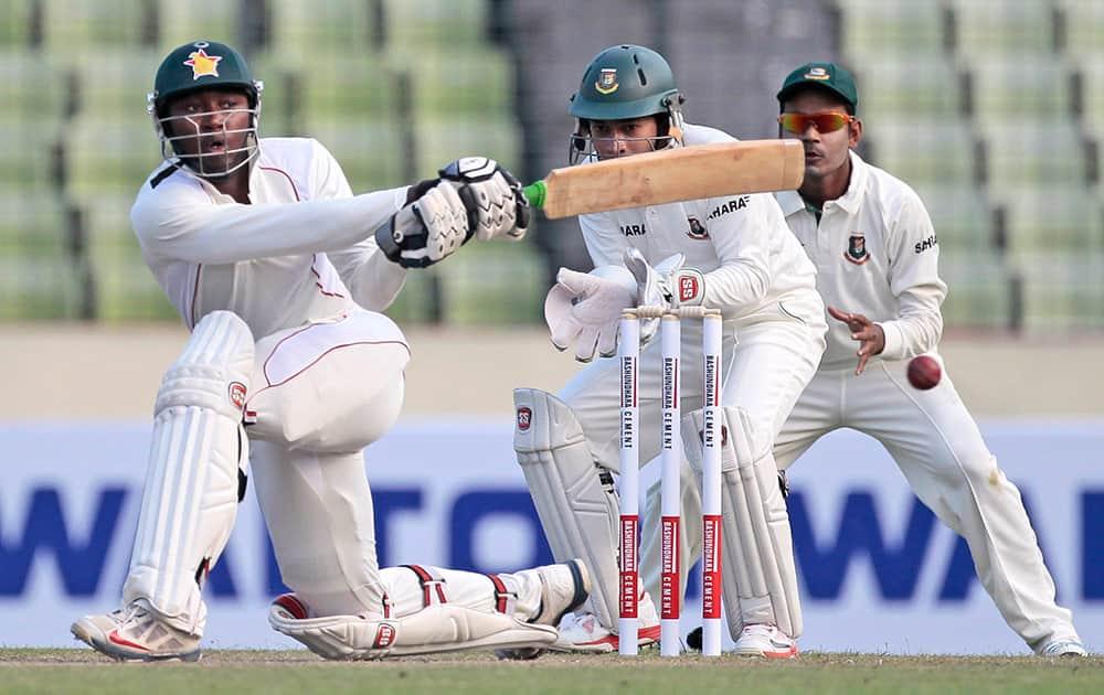 Zimbabwean cricketer Tinashe Panyangara, bats watched by Bangladesh's captain Mushfiqur Rahim and Shamsur Rahman during the first day of the first cricket test match in Dhaka, Bangladesh.
