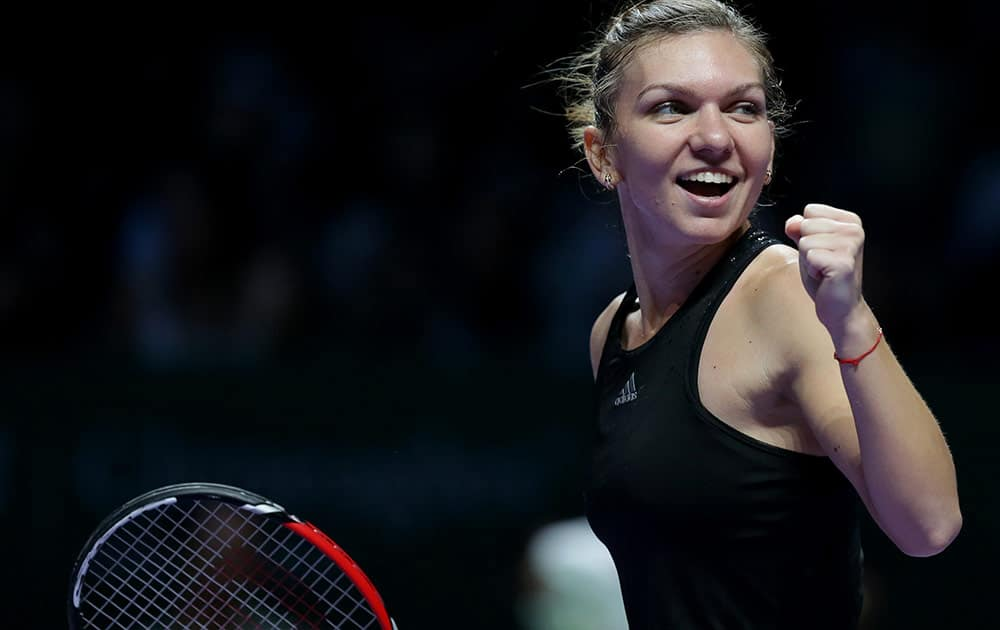 Romania's Simona Halep celebrates after defeating Poland's Agnieszka Radwanska in their semifinal match at the WTA tennis finals in Singapore.