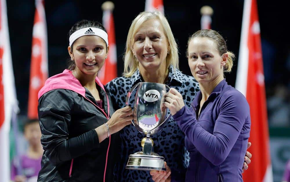 India's Sania Mirza, left, and Zimbabwe's Cara Black, right, stand with former champion Martina Navratilova and the trophy in her name after defeating Taiwan's Hsieh Su-Wei and China's Peng Shuai in the doubles final at the WTA tennis finals in Singapore.