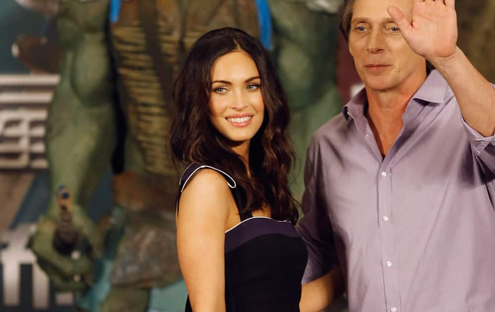 U.S. actress Megan Fox and actor William Fichtner pose for photographers on stage after attending a news conference for their latest movie
