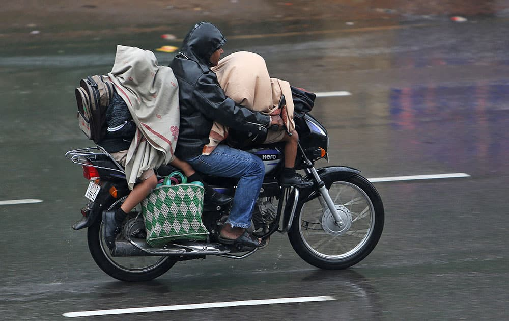 Schoolchildren cover themselves with shawls as they ride a motorbike in the rain in Hyderabad.