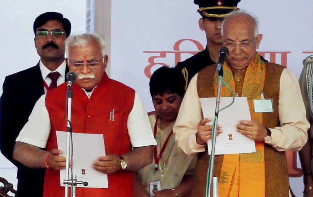Haryana Governor Kaptan Singh Solanki administers oath to the new Chief Minister Manohar Lal Khattar at a function in Punchkula.