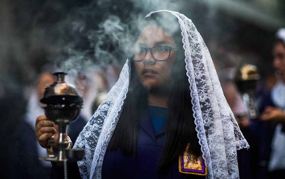 A woman carries a censer as during a procession honoring The Lord of Miracles `Senor de los Milagros` in Madrid, Spain.