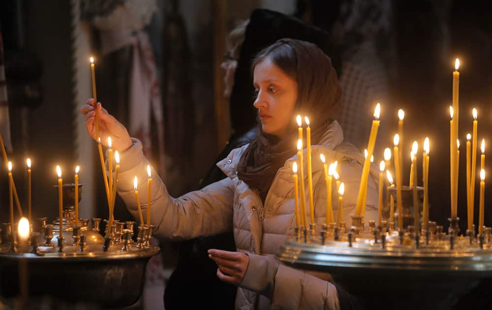 A woman lights candles at the St. Volodymyr Cathedral in Kiev, Ukraine. With more than one-third of the votes counted, two allied pro-European parties in Ukraine that ran on a platform to enact tough reforms took a joint lead Monday in a parliamentary election.