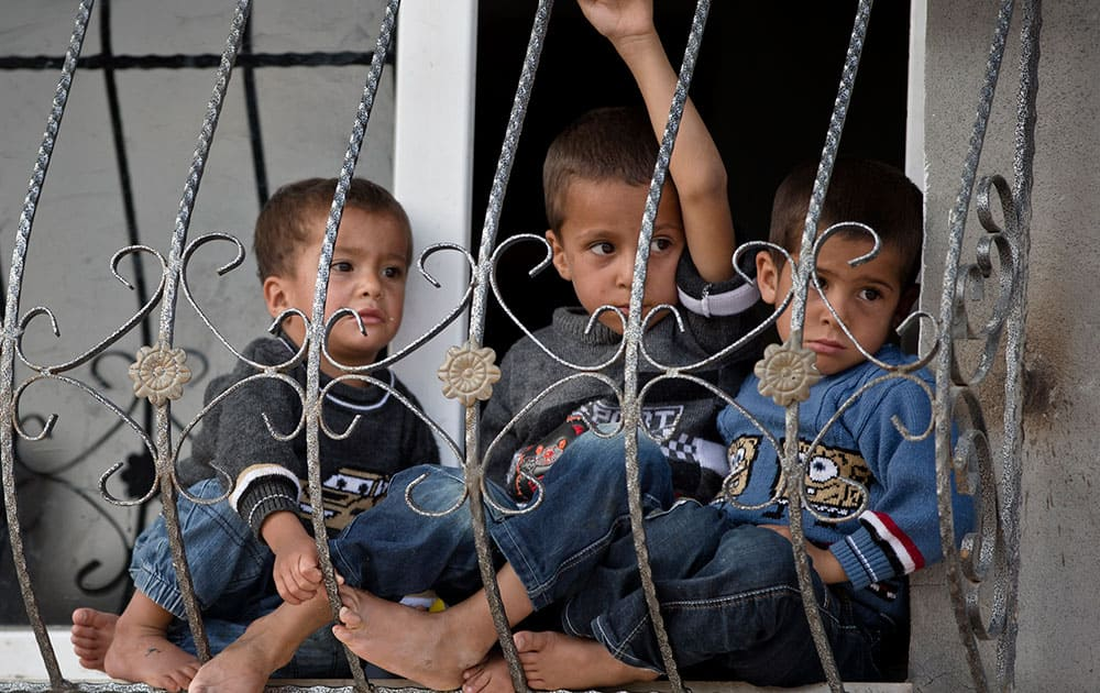 Kurdish children sit at a window in Suruc, on the Turkish side of the border with Syria, across from the Syrian town of Kobani.