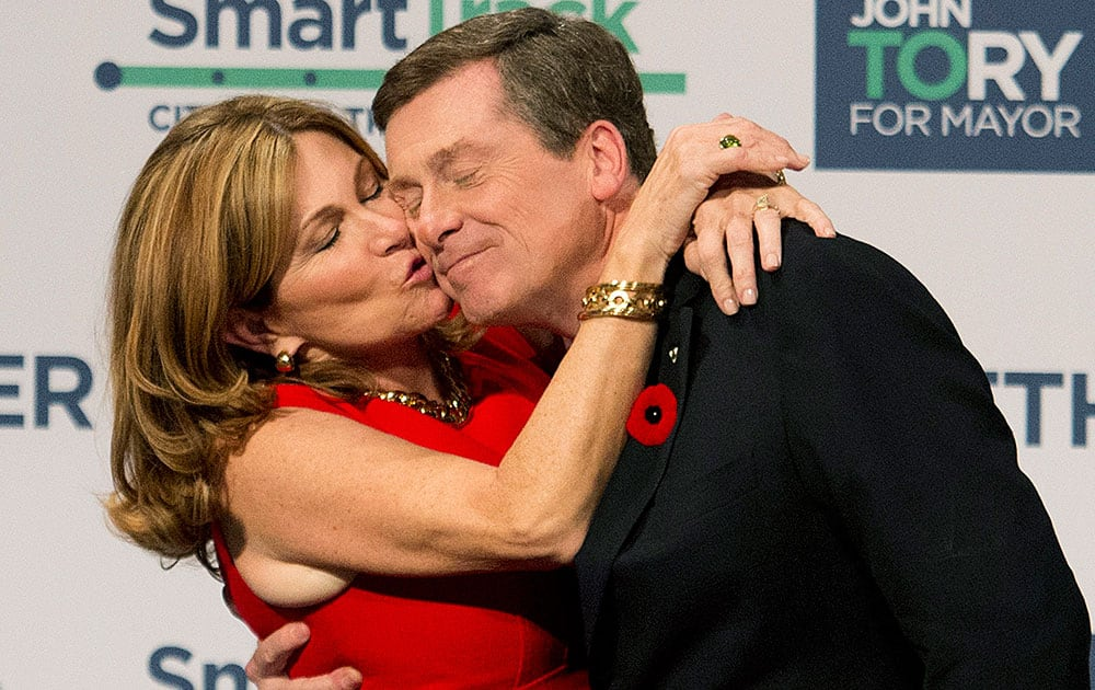 John Tory, right, receives a kiss from his wife Barbra Hackett after winning the election and becoming the new mayor of the City of Toronto.