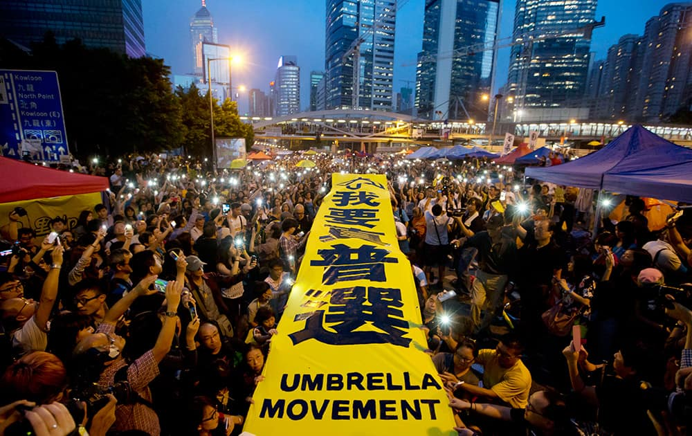 Pro-democracy protesters spread a yellow banner with the words reading: 'I want genuine universal suffrage' at a rally in the occupied areas outside government headquarters in Hong Kong's Admiralty.