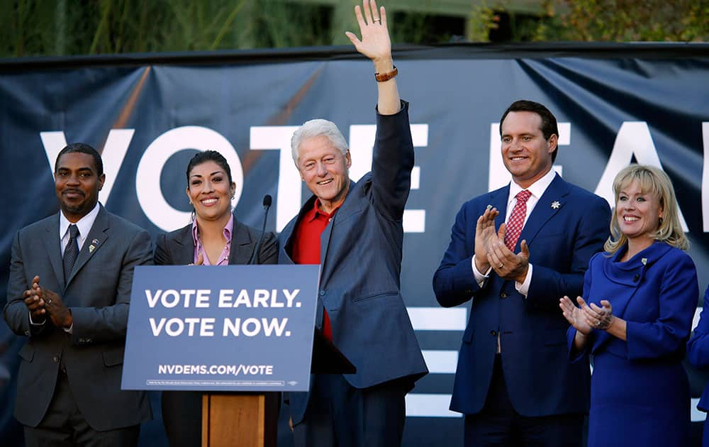 Former President Bill Clinton, center, waves during an event to support democratic candidates Rep. Steven Horsford, left, lieutenant governor candidate Lucy Flores, second from left, attorney general candidate Ross Miller, second from right, and congressional candidate Erin Bilbray in Las Vegas.