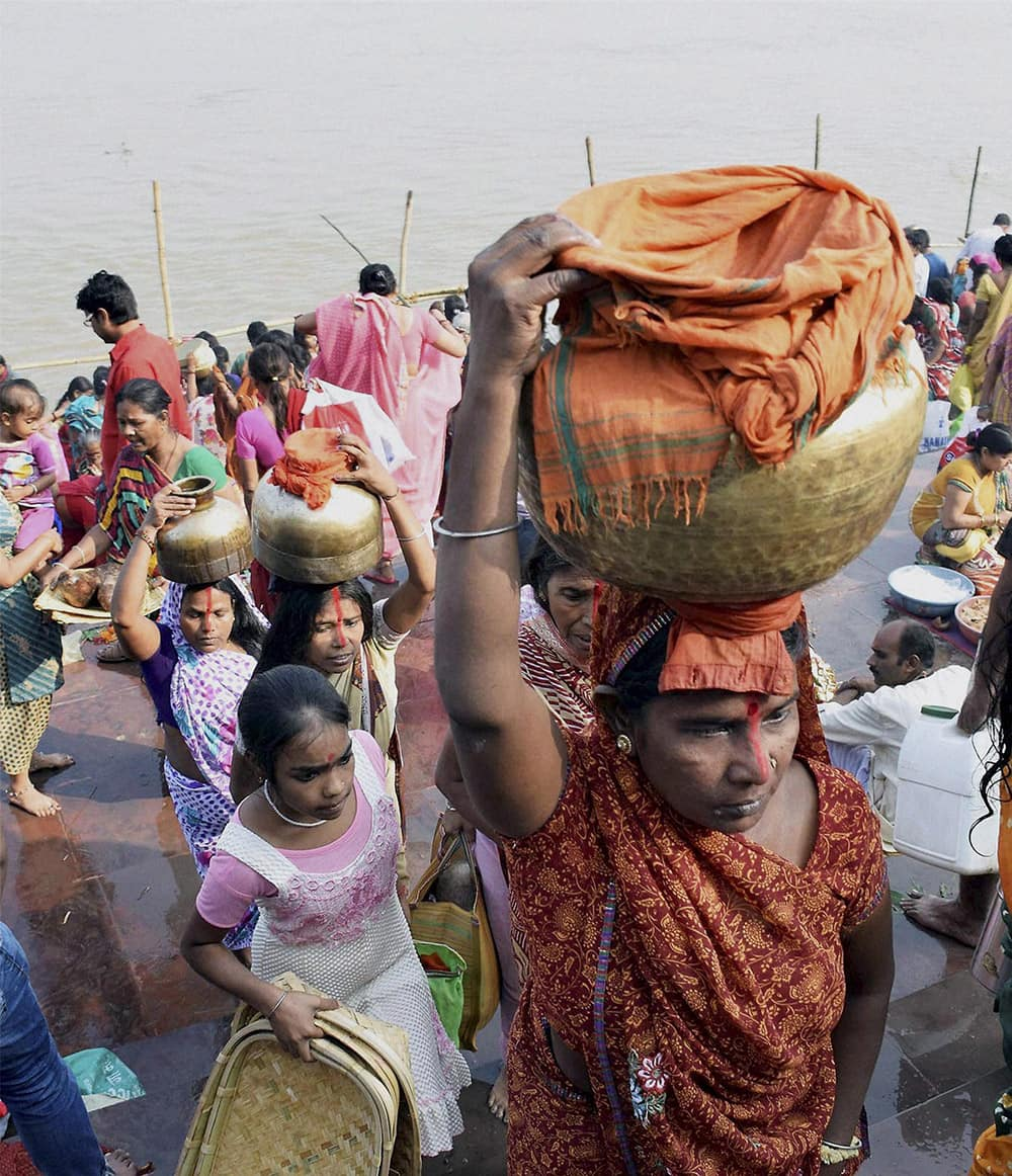 Women carry Ganga water for preparing prashad ahead of the four days long Chhath festiva,l in Patna.