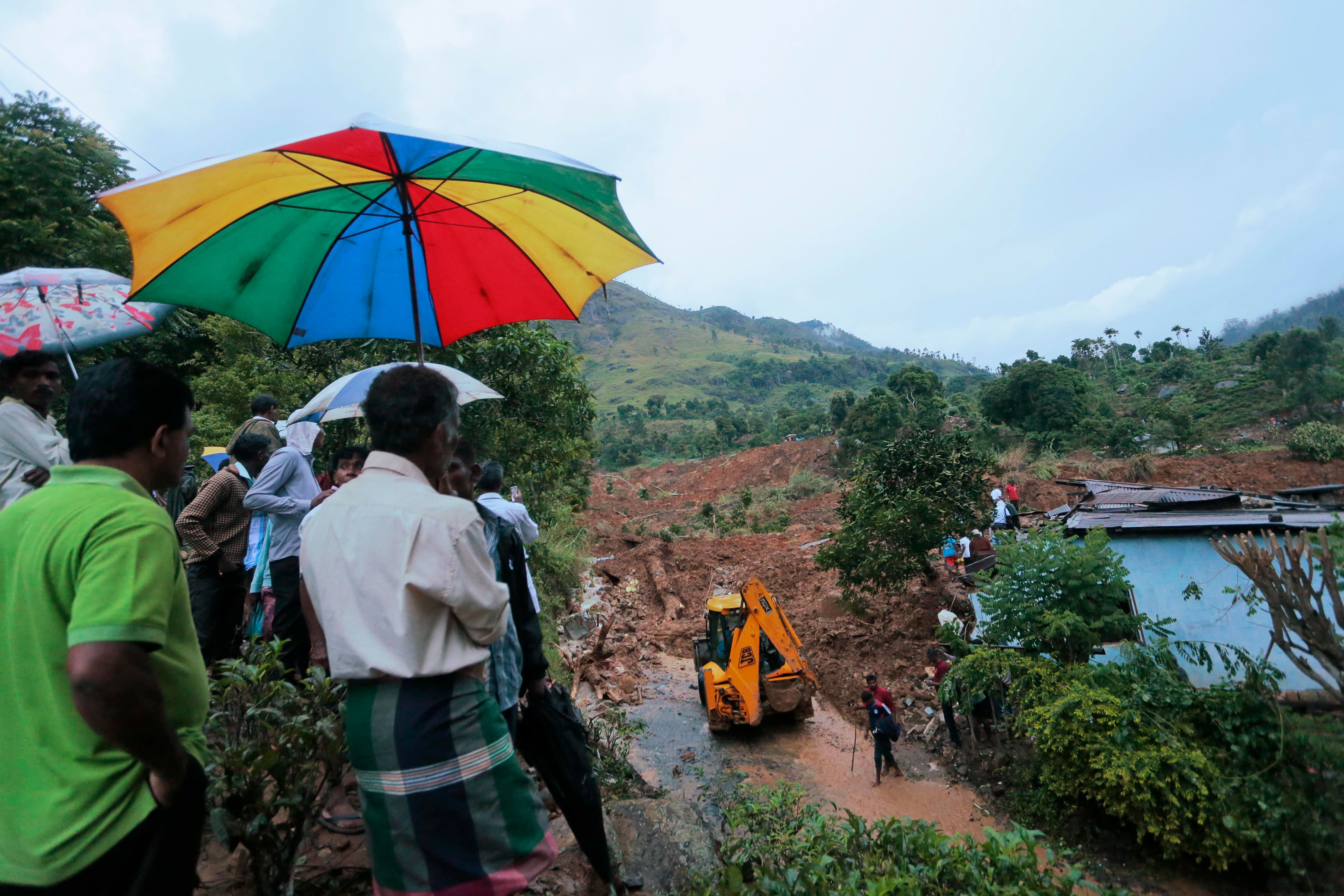 A crowd gathers as an earthmover clears debris caused by mudslide at the Koslanda tea plantation in Badulla district, about 220 kilometers (140 miles) east of Colombo.