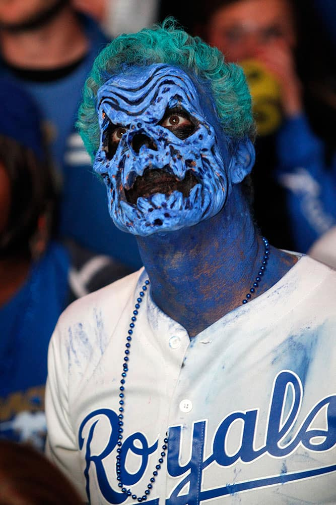Dressed for Halloween, a Kansas City Royals fan watches Game 7 of the World Series in the Power and Light entertainment district in Kansas City, Mo.