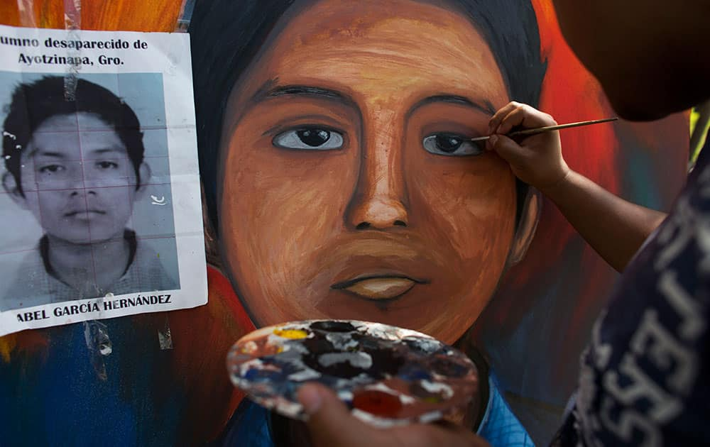 Local artist Florencio Sandoval paints a portrait of missing student Abel Garcia Hernandez, copying his likeness from his student photo, at the Isidro Burgos rural teachers college, in the Ayotzinapa district of Tixtla, Mexico.