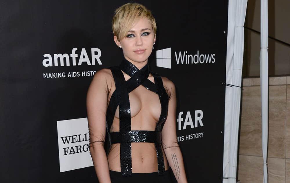 Miley Cyrus arrives at the 2014 amfAR Inspiration Gala at Milk Studios, in Los Angeles.