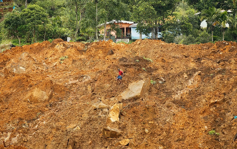 A Sri Lankan navigates his way though mud and sludge caused by a mudslide at the Koslanda tea plantation in Badulla district, about 220 kilometers (140 miles) east of Colombo.