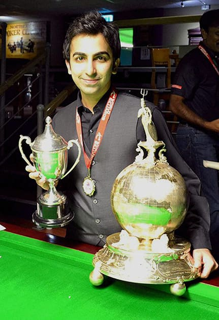 Pankaj Advani poses for photographs after winning the World Billiards Championship (time format) in Leeds.