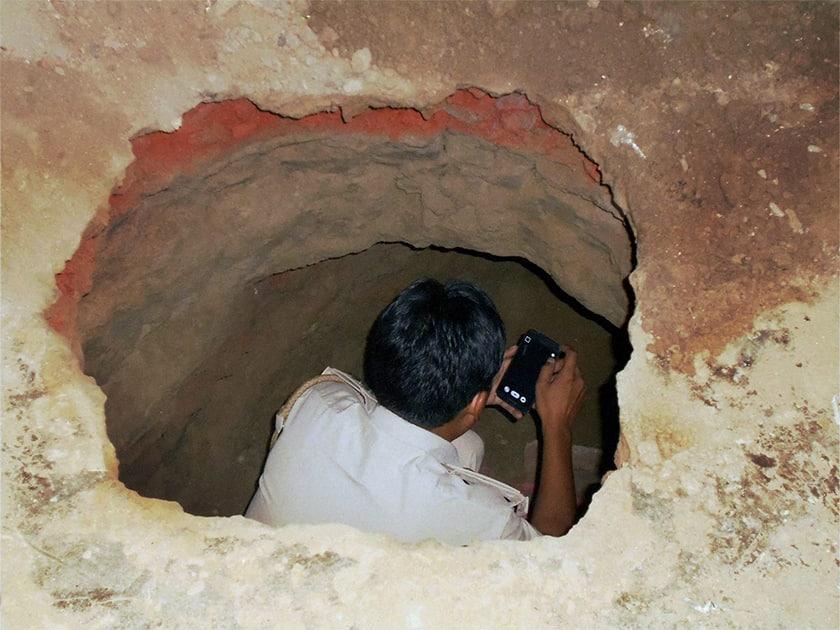 A police man investigates the tunnel dug up by the robbers in Gohana bank heist, in Sonipat.