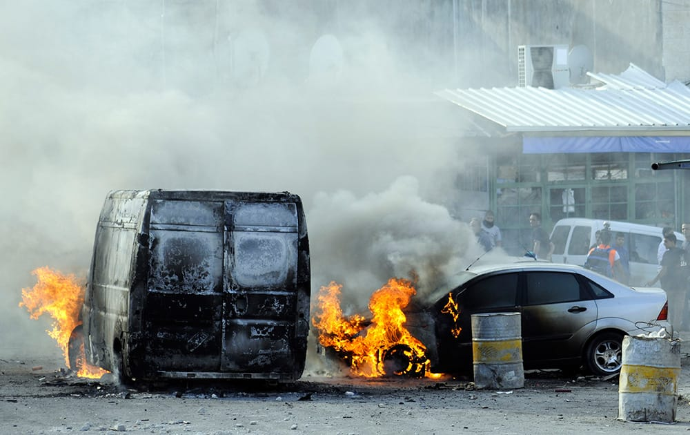 Cars are set on fire as Palestinians clash with Israeli border police after Moatez Higazi was shot in east Jerusalem.