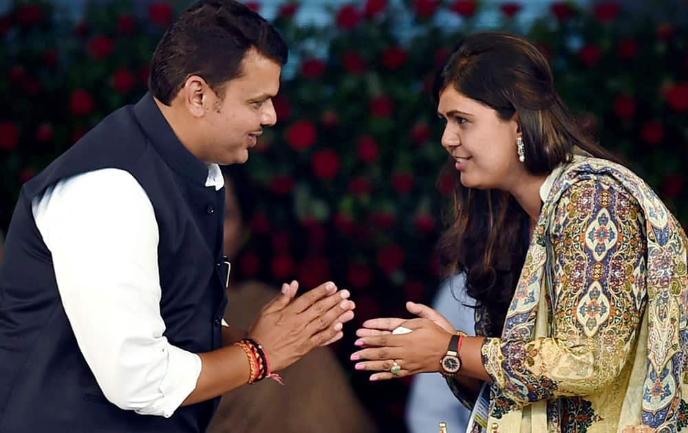 Maharashtra Chief Minister Devendra Fadnavis exchanges greetings with BJP Pankaja Munde at his swearing-in ceremony in Mumbai.