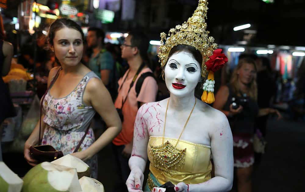 A tourist looks at a Thai woman dressed in a ghost costume for Halloween buying coconut in Bangkok.