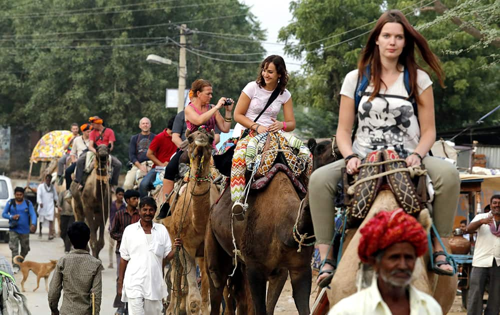 Foreigner tourists enjoy camel ride during the Pushkar Camel fair.