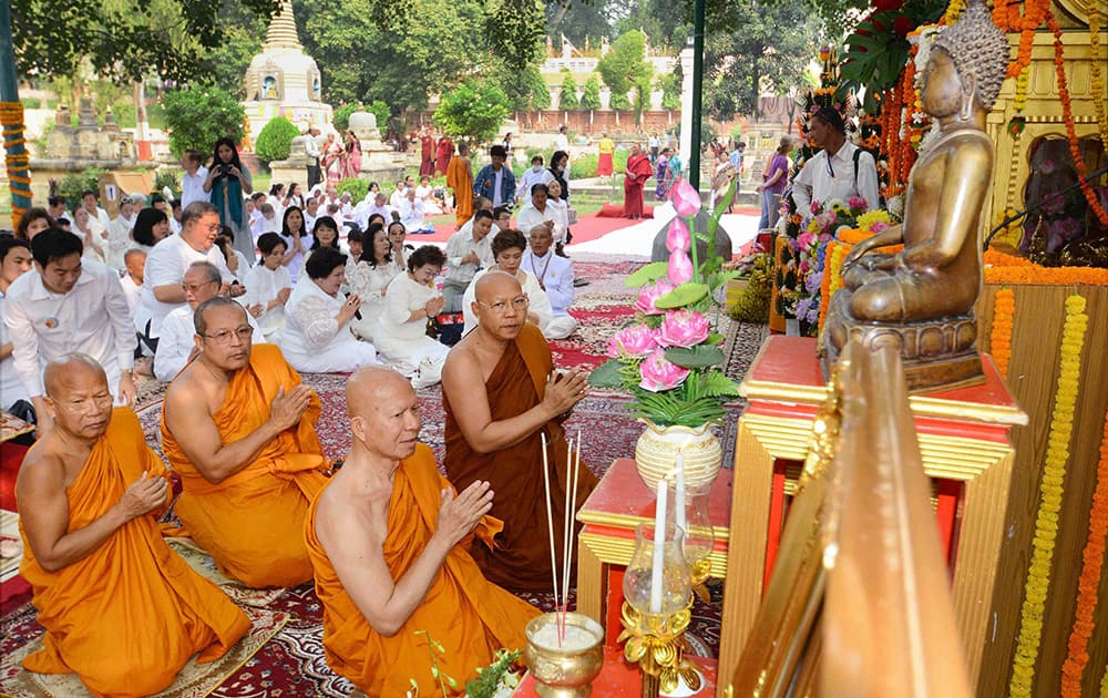 Monks and Thai devotees in the robe offering ceremony at Mahabodhi Temple in Bodhgaya.