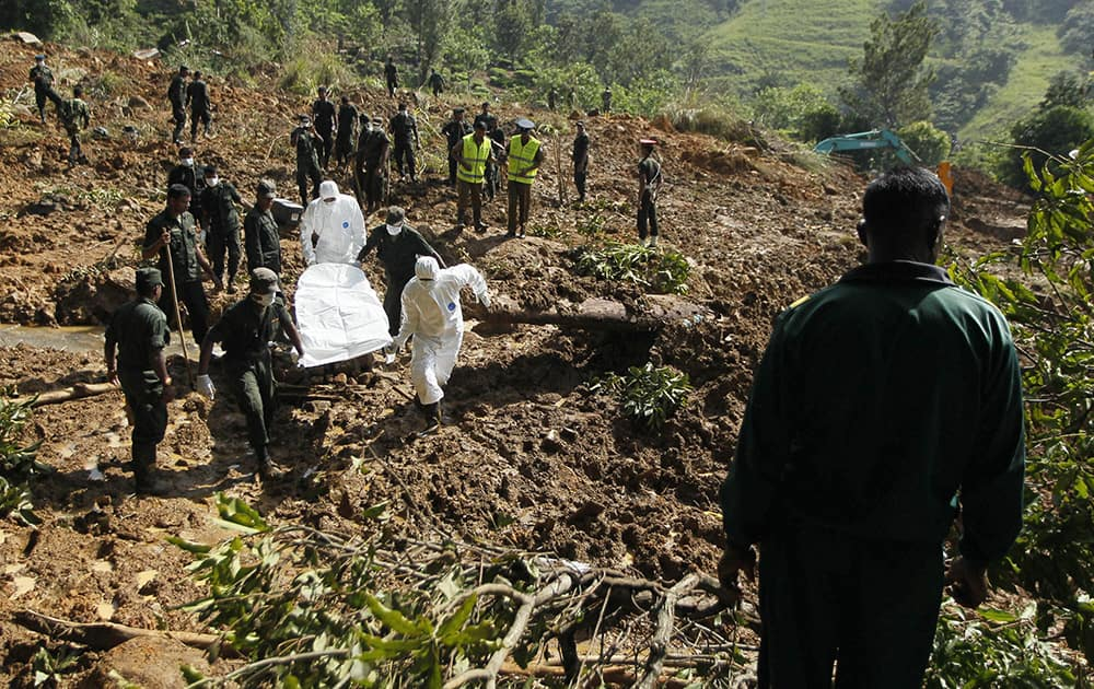 Sri Lankan army soldiers and forensic officers carry the body of a mudslide victim recovered from the site in Koslanda tea plantation in Badulla district, about 220 kilometers (140 miles) east of Colombo, Sri Lanka.