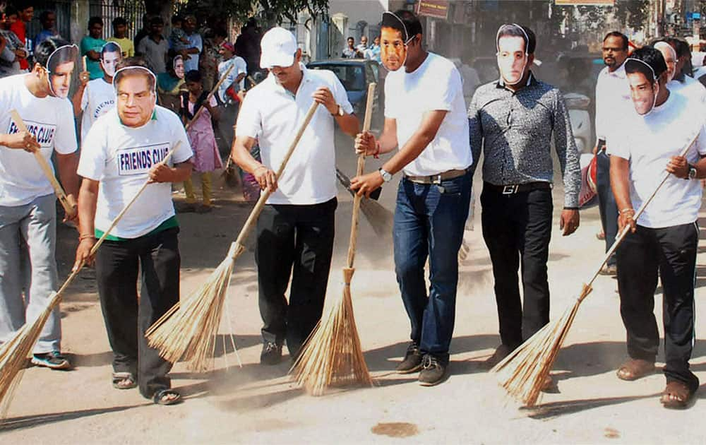 Members of Friends Club wearing masks of celebrities in a cleanliness drive during `swachh bharat abhiyan` in Guwahati.