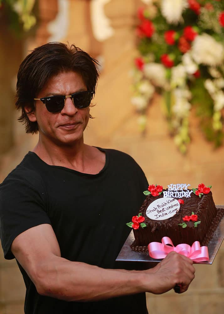 Bollywood superstar Shahrukh Khan poses with a cake on his birthday in Mumbai.
